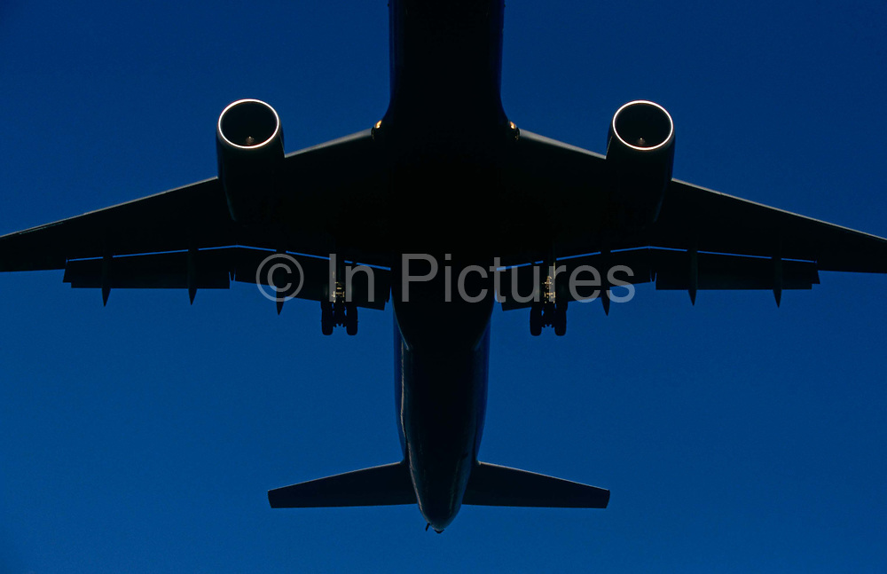 The outline of a generic airliner passes overhead as it takes-off at London Heathrow airport. With the strong shape of its aerodynamic surfaces, its wings and lowered flaps to gain maximum lift at this sea level atmosphere. The jet's undercarriage wheels are still lowered and the circular jet engines are clearly defined by strong sunlight. The airline operator is anonymous as is the manufacturer of the aircraft as it contunues its journey under blue skies to a faraway destination.