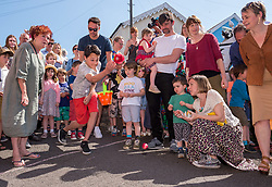 © Licensed to London News Pictures. 21/04/2019. Bristol, UK. Egg rolling contest on Vale Street, the steepest residential road in England which is held every year on Easter Day. The official gradient of Vale Street in Totterdown was recorded as having almost a 22-degree slope. The egg rolling, takes place on Easter Sunday at midday and is a decades-long tradition for local residents, who gather at the top of the road and roll hard boiled eggs to the bottom. Many of the hard boiled eggs end up broken or in the gutter. Photo credit: Simon Chapman/LNP