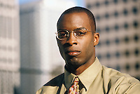 Portrait of African American business man.  Outside with city buildings in the background.<br />