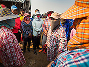 10 FEBRUARY 2016 - BAN LAEM, PHETCHABURI, THAILAND: Salt field workers get their final instructions from the foreman of their crew before starting the salt harvest in Phetchaburi province, Thailand. The salt harvest in Thailand usually starts in February and continues through May. Salt is harvested in many of the provinces along the coast, but the salt fields in Phetchaburi province are considered the most productive. The salt fields are flooded with sea water, which evaporates off leaving salt behind. Salt production relies on dry weather and producers are hoping the current drought will mean a longer harvest season for them.      PHOTO BY JACK KURTZ