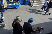 A man with blue hair that matches nearby shop fittings at Elephant & Castle in Southwark, on 28th March 2019, in London, England