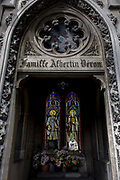 "Stained glass and arches in the Gothic mausoleum for the Albertin Deron family in the Pere Lachaise cemetery, Paris. Looking through the open arch with carvings and architectural features, we see inside to reveal flower pots and the stained glass of Saints Francois and Clothilde whose window has been broken to show other graves outside. Père Lachaise Cemetery (French: Cimetière du Père-Lachaise- or officially cimetière de l'Est, ""East Cemetery"") is the largest cemetery in the city of Paris, France (44 hectares (110 acres) containing the remains of a million French and foreign dead."