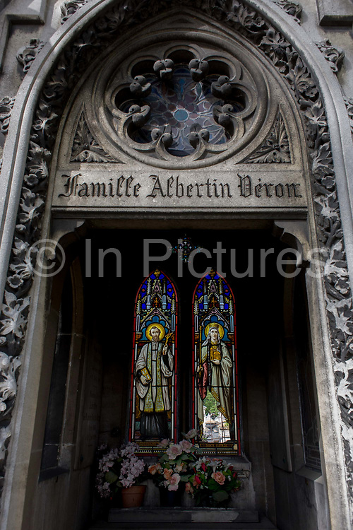 """Stained glass and arches in the Gothic mausoleum for the Albertin Deron family in the Pere Lachaise cemetery, Paris. Looking through the open arch with carvings and architectural features, we see inside to reveal flower pots and the stained glass of Saints Francois and Clothilde whose window has been broken to show other graves outside. Père Lachaise Cemetery (French: Cimetière du Père-Lachaise- or officially cimetière de l'Est, """"East Cemetery"""") is the largest cemetery in the city of Paris, France (44 hectares (110 acres) containing the remains of a million French and foreign dead."""