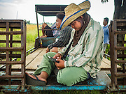 "23 NOVEMBER 2016 - AYUTTHAYA, THAILAND:   A farm worker checks his smart phone during the rice harvest in Ayutthaya province, north of Bangkok. Rice prices in Thailand hit a 13-month low early this month. The low prices are hurting farmers. Rice exports account for around 10 percent of Thailand's gross domestic product, and low prices frequently lead to discontent in the rural areas of Thailand. The military government has responded by sending soldiers to rice mills, to ""encourage"" mill owners to pay farmers higher prices. The Thai army and navy are also buying for their kitchens directly from farmers in an effort to get more money into farmers' hands.  PHOTO BY JACK KURTZ"