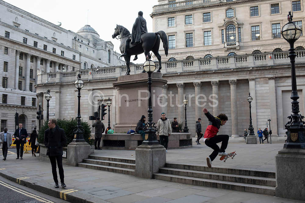 Skateboarder practices his moves near the Equestrian Statue of the Duke of Wellington at Bank in the City of London on 5th February 2020 in London, England, United Kingdom. The City of London is a city, county and a local government district that contains the historic centre and the primary central business district CBD of London.