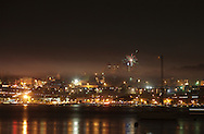 Beacon, New York -  A single firework explodes as smoke from the main Independence Day fireworks display drifts over Newburgh and the Hudson River as seen from a waterfront park on July 4, 2010. ©Tom Bushey / The Image Works