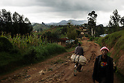 Pedestrians walk along a dirt road in the Nyamagabe District of Rwanda's Southern Province. The Mudasomwa Area Development Program (ADP) located here is one of many long-term development initiatives led by the international nonprofit World Vision. Area Development Programs work within communities like Nyamagabe over a period of several years, providing developmental resources to foster long-term, sustainable growth in the economic and physical well being of the community.