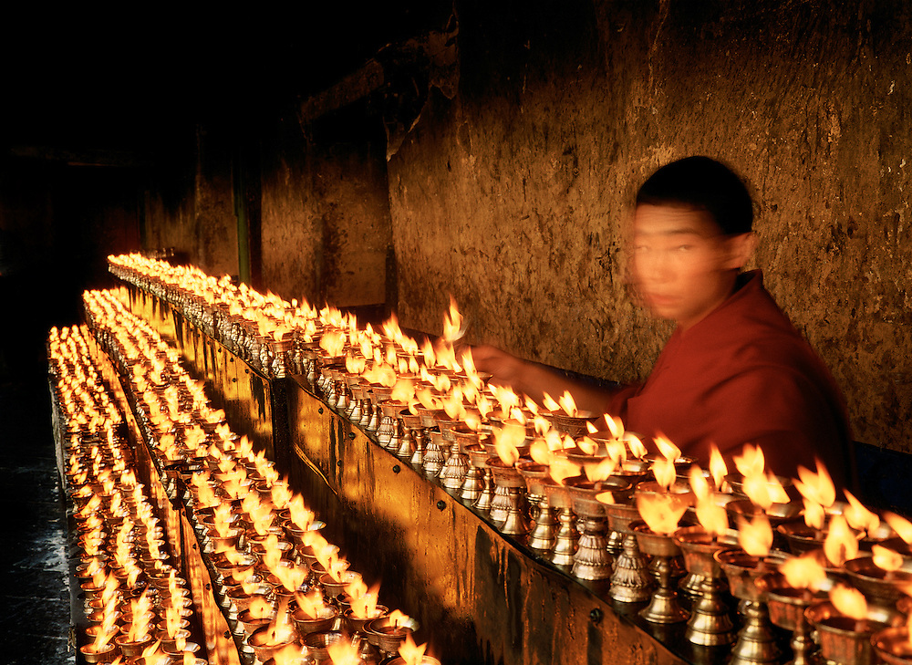 Novice monk lighting Tibetan Buddhist devotional butter lamps. The Jokhang Temple, Lhasa, Tibet.