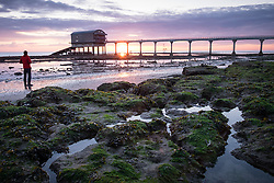 © Licensed to London News Pictures. 08/04/2016. Bembridge, UK. A man watching the colourful sunrise at Bembridge RNLI lifeboat station on the Isle of Wight this morning, Thursday 8th April 2016. Photo credit : Rob Arnold/LNP