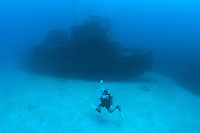 An enthusiastic dive master presents the wrecked tugboat, Beata..Shot in British Virgin Islands