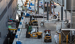 In the background, medical personnel take a sick passenger off of the Holland America cruise ship Zaandam on a stretcher, as workers in protective clothing unload luggage in the foreground, at Port Everglades, in Fort Lauderdale on Thursday, April 2, 2020. Holland America confirmed that a number of passengers are infected with the coronavirus.