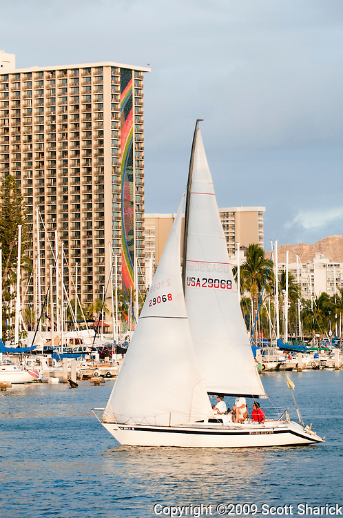 A sailboat sails into the Ala Wai Boat Harbor in Honolulu, Hawaii.