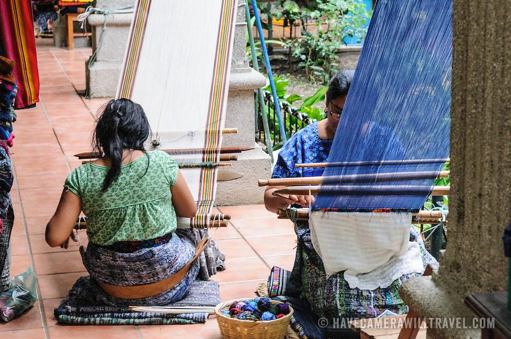 A woman weaving with a traditional backstrap loom in San Antonio Aguas Calientes near Antigua, Guatemala.