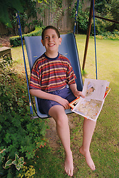 Teenage boy with autism reading book while playing on swing,