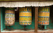 """In the Everest Area of Nepal, Asia: A prayer wheel (called mani chos-'khor or Mani wheel by the Tibetans) is a wheel on a spindle made from metal, wood, leather, or coarse cotton. On the wheel are written or encapsulated prayers or mantras. According to the Tibetan Buddhist belief, spinning such a wheel will have much the same effect as orally reciting the prayers. A prayer wheel symbolizes """"turning the wheel of Dharma,"""" which describes the way in which the Buddha taught. Published in """"Light Travel: Photography on the Go"""" book by Tom Dempsey 2009, 2010."""