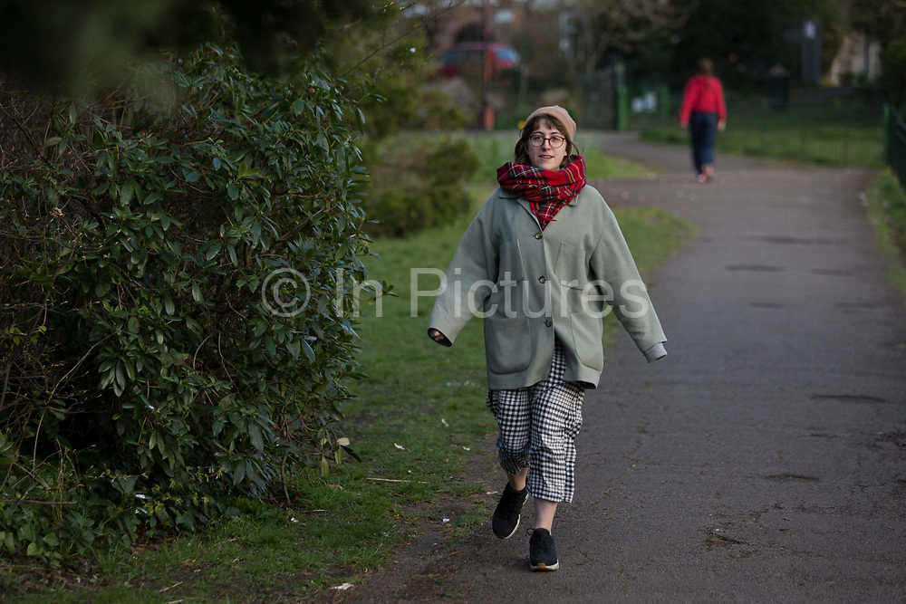 At the beginning of the second week of the UKs Coronavirus lockdown and in accordance with government guidelines for social distancing, family group isolation but local daily exercise, a yong woman practices sensible social distancing while enjoying fresh air in Ruskin Park, a green public space in the borough of Lambeth, on 30th March 2020, in south London, England.