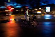 Een vrouw fietst 's avonds door Utrecht met een pakketje in haar fietskrat. De straten zijn nat van de regen.<br /> <br /> A woman cycles in Utrecht on an evening, with a post package. The streets are wet due to the rain.