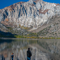 A father and daughter fish in Convict Lake in the eastern Sierra Nevada near Mammoth Lakes, California.  Behind is Laurel Mountain.