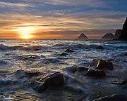 """The sun sets over waves of the Pacific Ocean near winter solstice at Three Arch Rocks, Oceanside, Oregon, USA. Published in """"Light Travel: Photography on the Go"""" by Tom Dempsey 2009, 2010."""