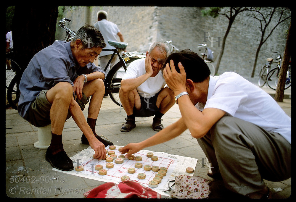 Men use sidewalk outside the Forbidden City to play a game that resembles checkers; Beijing. China