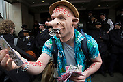 Demonstrators outside the Great Connaught Rooms where the Conservative Party Spring Conference was taking place and protesters gathered against David Cameron's links to offshore finances on April 9th, 2016 in London, United Kingdom. One protester wearing a mask with the word GREED on it began to pose with fake money. Thousands of protesters gathered calling for the Prime Minister to resign and to protest over his recently revealed tax dealings in the Panama Papers'.