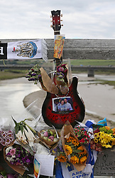 © Licensed to London News Pictures. 02/09/2015. Shoreham, UK. A guitar is left with flowers and photographs in tribute to Daniele Polito on a bridge near the site of the crashed Hawker Hunter fighter jet. The aircraft crashed while performing at the Shoreham air show on August 22, 2015 killing 11 people on the ground. As an inquest into the deaths opened today in nearby Horsham, the name of the last of the victims Graham Mallinson was released.  Photo credit: Peter Macdiarmid/LNP