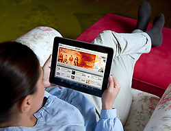 Woman using iPad tablet computer to browse digital online iTunes music store