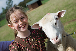 Young girl stroking a sheep on a visit to a city farm,