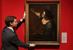 An employee of the Royal Collection Trust adjusts Artemisia Gentileschi's Self-Portrait as the Allegory of Painting, which is on display in the Portrait of the Artist exhibition at the Queen's Gallery, Buckingham Palace, London.