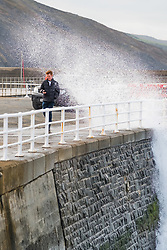 ©Licenced to London News Pictures - Aberystwyth, UK. 30/09/2018. A young man gets splashed by the spray a blustery cold winds at high tide bring big waves crashing against the  harbour wall in Aberystwyth on the Cardigan Bay coast, west Wales on the last day of September 2018<br /> Photo  cerdit: Keith Morris / LNP
