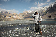 A young duck hunter looks for cartridge. Hussaini village, Gojal region.