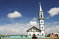 """Portrait of a church that Father Sebastian Obermaier built in El Alto, Bolivia. a town he has lived in for 27 years .  """"I don't feel Bolivian, I feel Aymara"""" he says, referring to the Aymara indigenous population that makes up more than 80% of El Alto. Father Obermaier has been designing and building churches in El Alto for the past 10 years, with a goal of building one church for every 10,000 inhabitants of the city, which currently has nearly 700,000 people living in it.  Everyone that visits Bolivia can see his numerous churches from the window of their airplane as it lands in El Alto.  The churches are marked by a style unique to Father Obermaier, that mixes indigenous symbols with tall towers and bright colors, that leave every church looking different, as if they were straight out of a children's pop-up book."""