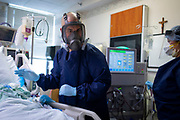 Phil Weckerly, an ICU nurse, and patient care technician Jenny Valenzuela monitor a COVID-19 patient receiving dialysis Monday, May 11, 2020 at St. Anthony Hospital. (Brian Cassella/Chicago Tribune)