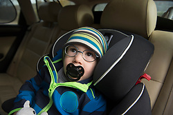 Little boy with pacifier in his mouth sitting in car seat