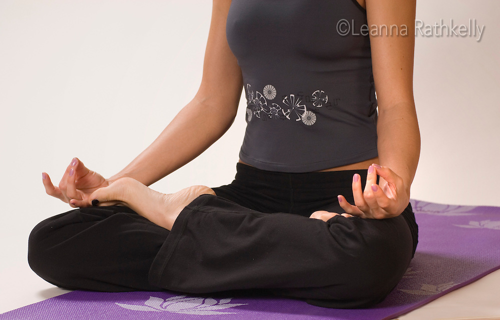 A woman meditates with her legs crossed in yoga position