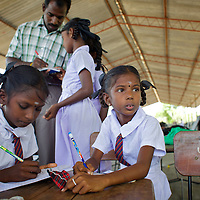M. Dilushana, age 9 (looking up) in class in a UNICEF-supplied Temporary Learning Space.<br /> <br /> Sisters M. Dhanushika, age 11 and M. Dilushika, age 9 are from Sri Lanka's Tamil community. They lost their mother in 2006 after she was raped and killed, allegedly by TMVP troops loyal to Colonel Karuna. Their father has subsequently remarried and refuses to be involved in the upbringing of his daughters who live together in a temporary makeshift shelter supplied by UNHCR. The two sisters rely on their aunt and uncle for care. Dhanushika and Dilushika attend Vadamunai Government Tamil Mixed School but often miss classes because they must work collecting reeds which provides them their only source of income. Despite the challenges of their situation, Dhanushika is a particularly conscientious child. As well as taking responsibility for her own necessities, she is committed to her sister's well being. The girls rely on a meal provided by the school every day. Despite the support of neighbours, their present situation is not sustainable and they are likely to be admitted to the care of an orphanage in the near future. <br /> <br /> When fighting between the LTTE and Colombo Government forced the displacement of the local Tamil community in 2007, the Vadamunai Government Tamil Mixed School in Batticaloa District was closed. Since reopening in January 2009, the school has six teaching staff for 88 pupils from Grades 1-9. Before closure,136 pupils studied at the school. Poor road-infrastructure and the remote location of the school means that many staff have to commute for more than three hours. Five classes are held in a UNICEF-supplied Temporary Learning Space. Four other classes are conducted outside, beneath trees. Many of the students suffer with the trauma and stress associated with those living in conflict situations. The staff must deal with these issues as well as the personal difficulties that they themselves suffer living in a conflict environment. To further 