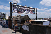 People pass a large scale billboard advertising poster as work continues at the construction site for the HS2 mainline station at Curzon Street on 14th July 2021 in Birmingham, United Kingdom. The Curzon Street Masterplan covers a 141 hectare area of regeneration, focussed on HS2 Curzon Street station in Birmingham city centre, combined with approximately 700 million in investment into the surrounding area including new homes and commercial developments. High Speed 2 is a partly planned high speed railway in the United Kingdom with its first phase in the early stages of construction, the second phase is yet to receive full approval and the third is subject to merging with Northern Powerhouse Rail, a separate project.