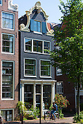 Man cyclist with smartphone by canalside gabled houses - Dutch gables - on Brouwersgracht in Amsterdam, Holland