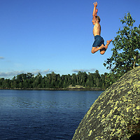 SWIMMING. 8-year old Nick Wiltsie (MR# W-11) jumps off cliff, Lake of the Woods Ontario, Canada.