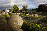 A wide view of the graveyard in the cemetery of Church of the Holy Rude in Stirling, Scotland. It is one of the town's most historically important buildings. It was rebuilt in the 1400s after Stirling suffered a catastrophic fire in 1405, and is the only surviving church in the United Kingdom apart from Westminster Abbey, to have held a coronation. On 29 July 1567 the infant son of Mary, Queen of Scots, was crowned James VI of Scotland here. Musket shot marks from Cromwell's troops during the War of the Three Kingdoms are clearly visible on the tower and apse. Another important historical religious site in the area is Cambuskenneth Abbey.