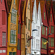 Bryggen (Norwegian for the Wharf), also known as Tyskebryggen (the German Wharf) is a series of Hanseatic commercial buildings lining the eastern side of the fjord coming into Bergen, Norway. Bryggen has since 1979 been on the UNESCO list for World Cultural Heritage sites. These historic shops were a challenge to shoot because they are so crooked. I used a zoom to compress the scene and allow me to get more of them in the shot. This was one of my favorite shots of  the bryggen.