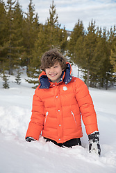boy standing in deep snow on a mountain
