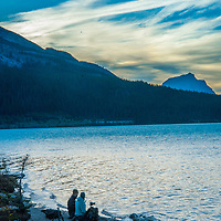 Photographers shoot dawn breaking over Bow Lake in Banff National Park, Alberta, Canada. Behind is  Mount Andromache, ®.