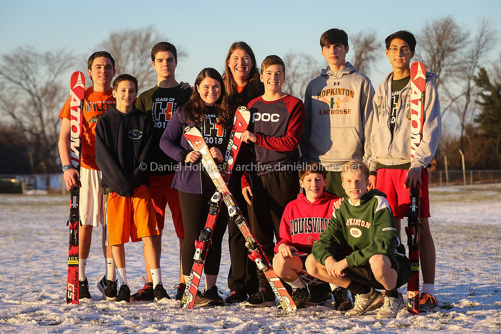 (12/5/16, HOPKINTON, MA) Hopkinton ski coach Nancy Schlussel, center, poses with some of her team members from left, Pat Murphy, Jack Rodgers, Max Siegfried, Molly Doherty, Kyle Perkins, Jordan Hanna, and David Antaki; front Max Rodgers, and Will Hutchinson at Hopkinton High School on Monday. Daily News and Wicked Local Photo/Dan Holmes