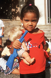 Young girl standing in nursery school playground holding doll and toy gun,