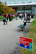 Brooklyn, NY – 24 October 2020. A line of people eager to vote stretched for 0.6 mile (1 km) a half hour after the polls opened on the first day of early voting in New York. The doors at the early voting location at Brooklyn College in the Midwood neighborhood opened for voters at 10:00 AM, and a poll worker reported that the first person to arrive got to the doors at 4:30 that morning. The entrance to the polling place at Brooklen College.