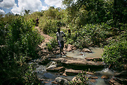 Nyajouk Chuol Bil, 18, crosses the river as she heads to a school run by UNHCR inside Bidibidi refugee settlement in Uganda. When a small fighting broke out in the summer of 2015, she hid in the UN compound in Juba. When she went outside the compound to buy sandals, she was met with four Dinka soldiers with AK-47. She got pregnant from the rape and gave birth to a daughter. She was separated from her parents and hasn't heard the whereabout of them.  Now a senior 1 grade in the secondary school, she goes to school inside the refugee camp, but worries that there's very few people who could babysit the baby when she is away. She said she wanted to be an accountant or work in a bank in the future.