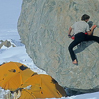 Alex Lowe climbs on a boulder at the base camp for big wall climbing expedition up Great Sail Peak (not visible) on Canada's Baffin Island.