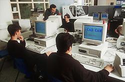 Secondary school teacher and pupils in computer technology class,