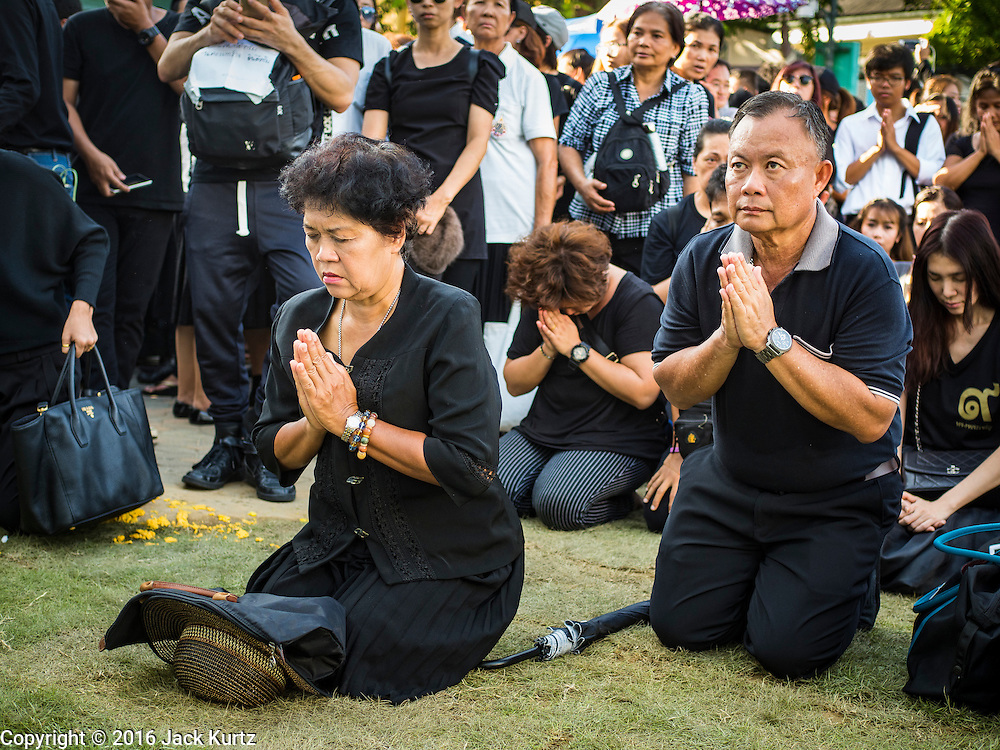 15 OCTOBER 2016 - BANGKOK, THAILAND:  People in mourning pray in front of the Grand Palace for Bhumibol Adulyadej, the King of Thailand. King Bhumibol Adulyadej died Oct. 13, 2016. He was 88. His death comes after a period of failing health. With the king's death, the world's longest-reigning monarch is Queen Elizabeth II, who ascended to the British throne in 1952. Bhumibol Adulyadej, was born in Cambridge, MA, on 5 December 1927. He was the ninth monarch of Thailand from the Chakri Dynasty and is known as Rama IX. He became King on June 9, 1946 and served as King of Thailand for 70 years, 126 days. He was, at the time of his death, the world's longest-serving head of state and the longest-reigning monarch in Thai history.     PHOTO BY JACK KURTZ